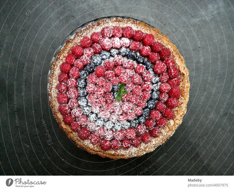 Delicious fruit cake with raspberries, blackberries and powdered sugar on a dark grey concrete floor in a designer apartment in Rottenbuch in the district of Weilheim-Schongau in Upper Bavaria