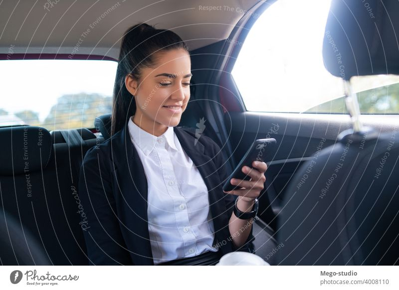 Businesswoman using mobile phone in car. businesswoman taxi transportation cab male portrait adult professional auto going to work wireless entrepreneur elegant