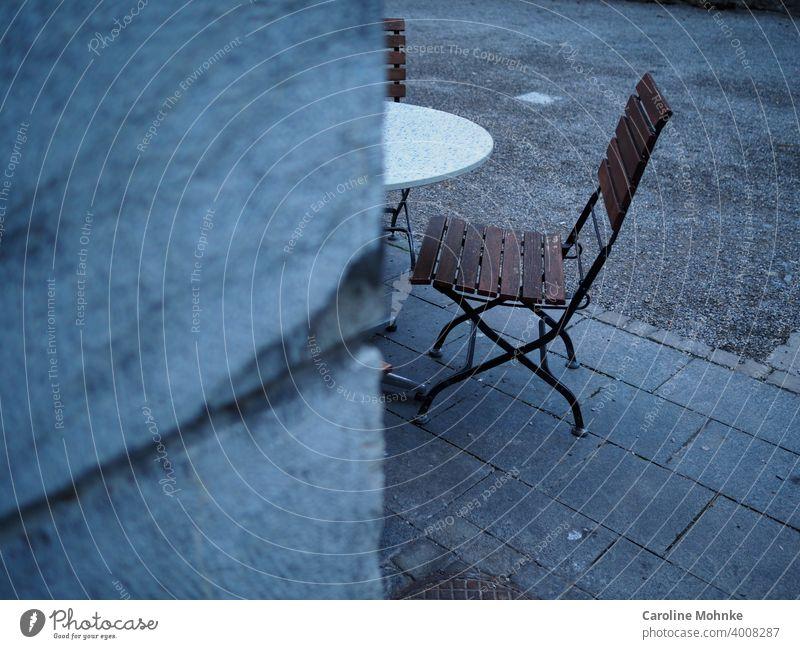 Blick um die Ecke auf Bistrostühle und Tisch-ein geschlossenes Strassencafe Stuhl Stühle lockdown Coronavirus Restaurant COVID Virus Vorsorge Quarantäne