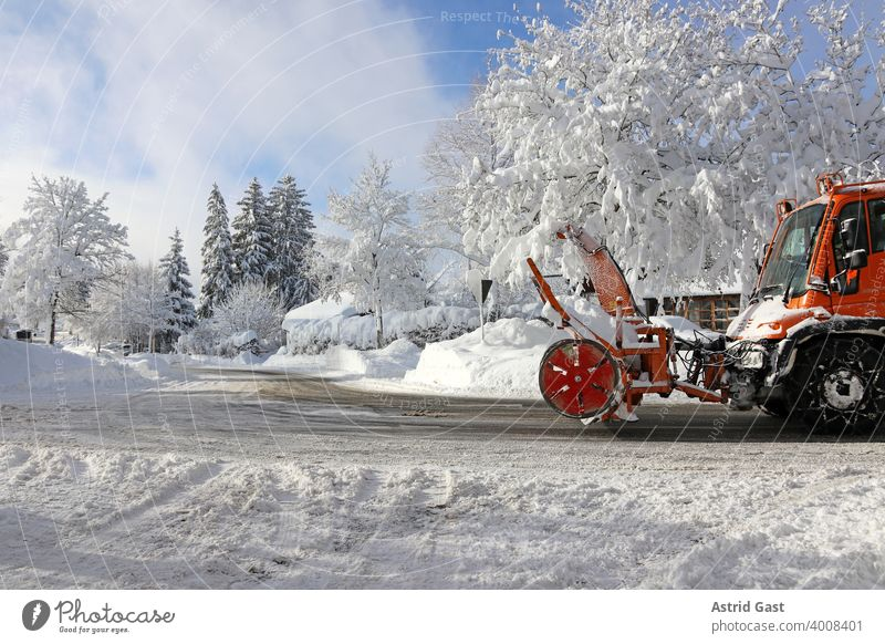 A snow plough with a snow blower drives through the street in a city in winter to clear away the high snow Winter Snow Street Town Snowy flight spacecraft