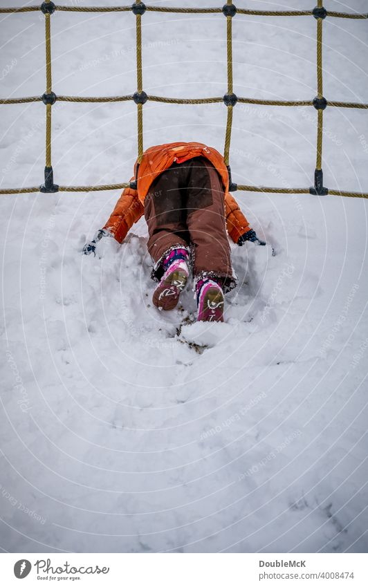 A child lies in the snow and plays in the playground net Day Exterior shot naturally depth blur Life Joy Cold cold season Snow look away Winter chill 1