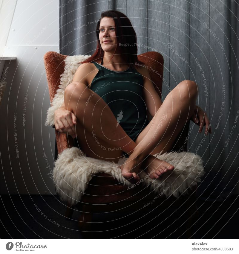 young woman sits cross-legged on an armchair with sheepskin and looks at the window Legs Barefoot Long-legged Laughter petrol Dress Drape Skin Colour photo