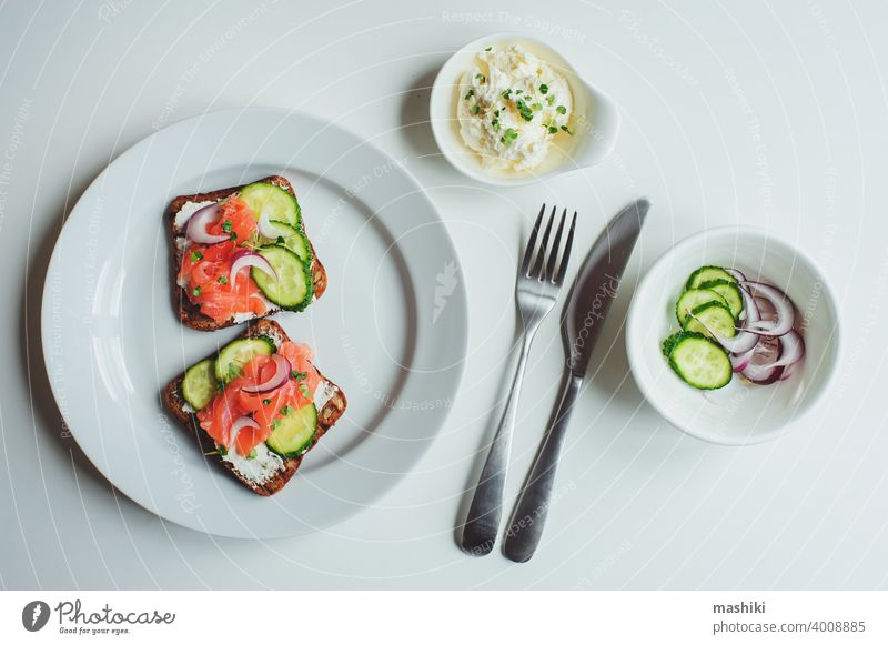 tasty healthy breakfast - salmon and avocado toast with cream cheese, cucumber and red onion on white background food sandwich bread snack meal fish lunch
