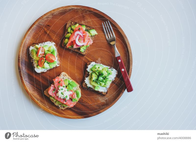 tasty diet food for breakfast or brunch - avocado and salmon toast with cream cheese, cucumber and red onion served on wooden plate sandwich bread snack meal