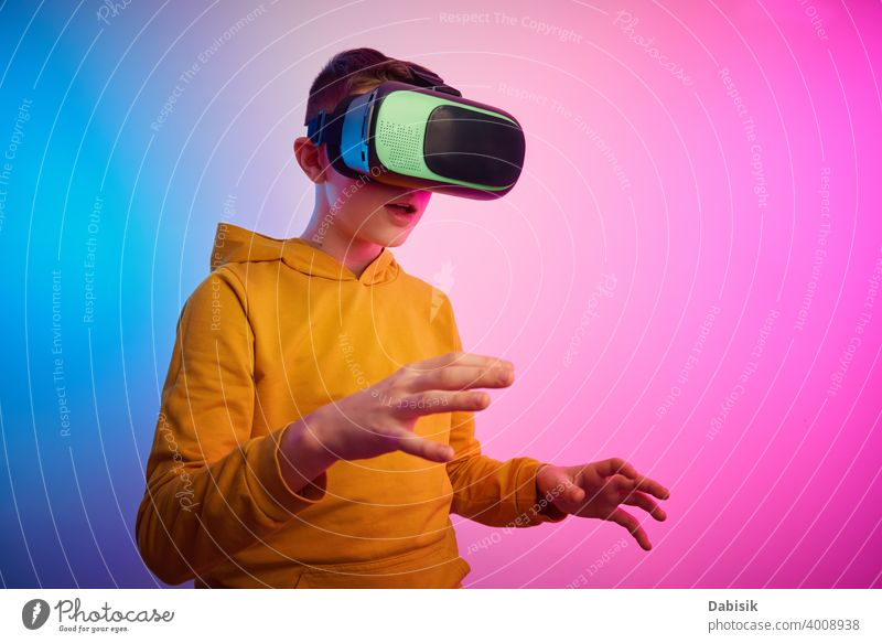 Boy with virtual reality glasses on colorful background. Future technology, VR concept vr headset boy helmet device game future video experience wearable