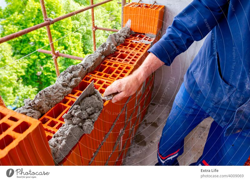 Builder using spatula to set up mortar over red brick Accuracy Accurate Apply Block Brick Bricklayer Bricklaying Brickwork Building Site Civil Engineering