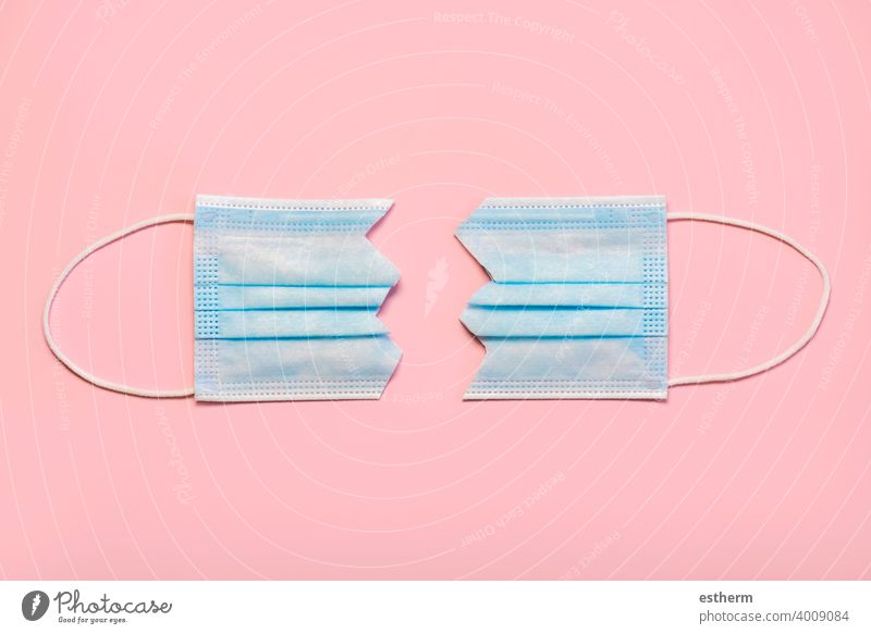 Protective surgical mask split in two.Concept of protesting against coronavirus scams protective surgical mask coronavirus masks medical face masks