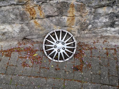 Lost silver hubcap in the style of a light alloy rim on old grey pavement in front of natural stone masonry in Oerlinghausen near Bielefeld in the Teutoburg Forest in East Westphalia-Lippe