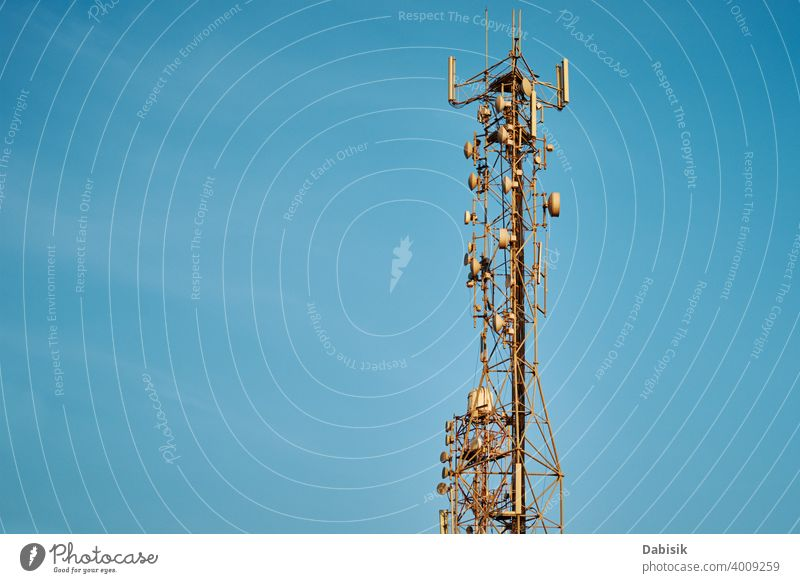 Communication tower with antennas against blue sky cell broadcast radio telecommunication network mobile technology wireless transmitter metal phone frequency
