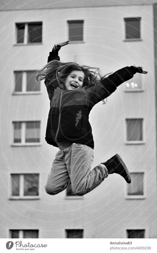 joyful leaps Jump Hop Girl Winter Cold Joy Tall Black & white photo Long-haired Child Infancy Anticipation Dance Happy fortunate yeah Skip