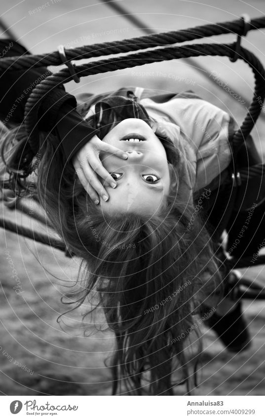 I can't think of a name. Girl Playing Playground Climbing Black & white photo portrait Child Infancy Youth (Young adults) go out peep Hang Cold Winter Face