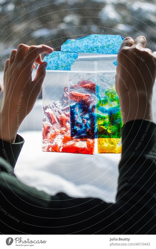 Special needs child holds zip lock baggies of colored gel up to a window to learn about primary colors, color mixing, and sensory play hand touch color theory