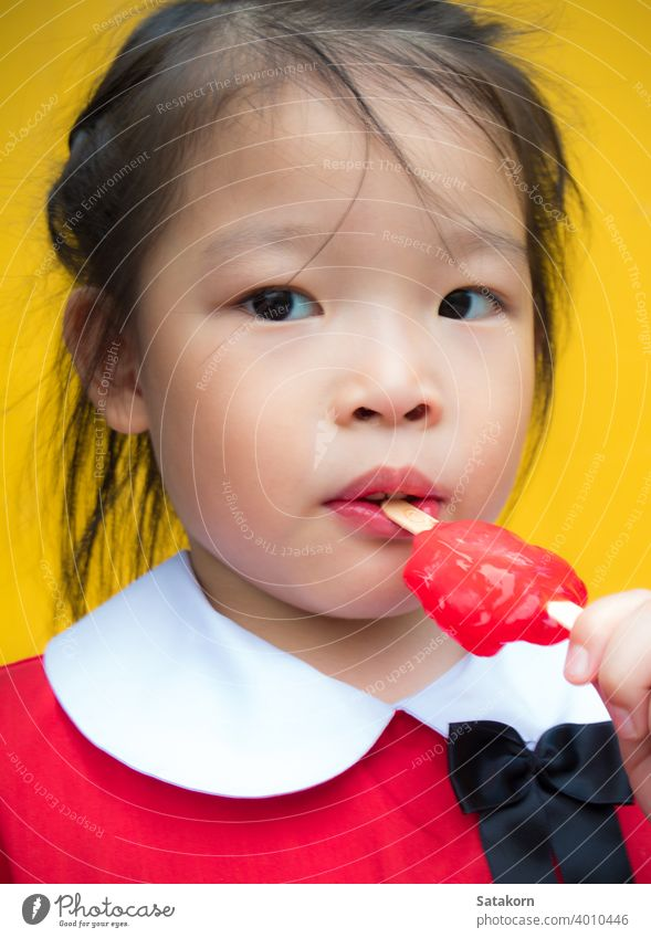 Little girls in red student dressed Eating a red popsicle little cute sweet eat young background food happy fun dessert ice cream lolly portrait beautiful kid