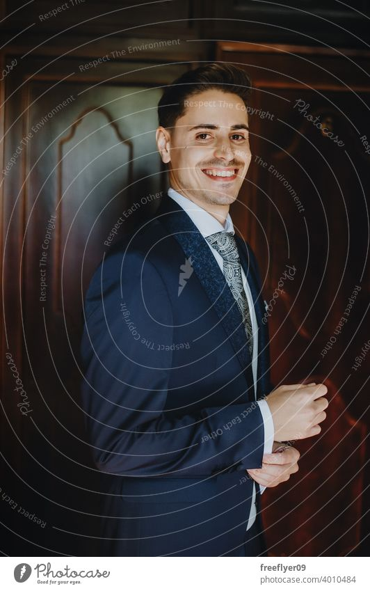 Portrait of a young groom on his wedding day smiling at camera portrait marriage engagement people attractive copy space looking at camera man male 20s 30s blue