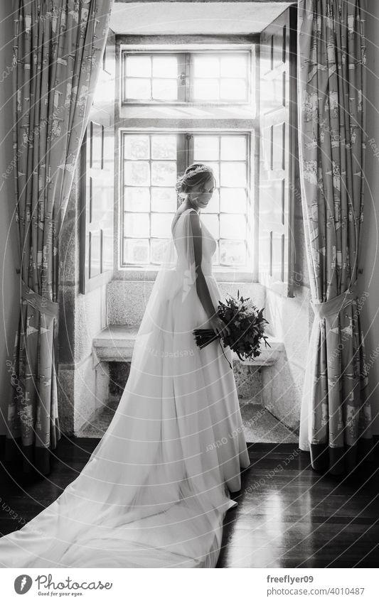 Bride on her wedding dress in front of a window marriage bride love woman fine elegance caucasian person beauty female femininity portrait event romance human