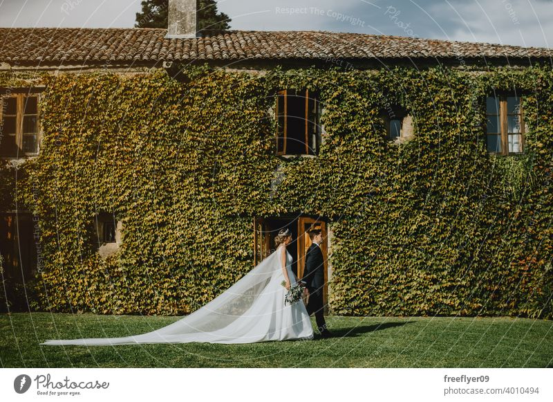 Couple on ther wedding day in front of a wall full of climbing plants marriage engagement bride people young attractive copy space pazo galicia ancient castle