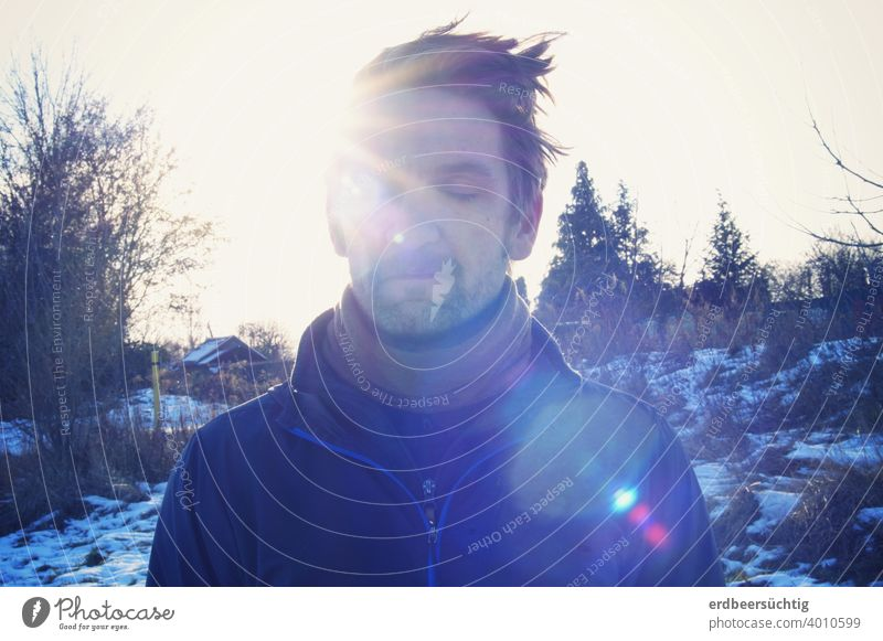 Man refueling in the sun Sun rays Face hair Cold chill warming Closed eyes Glare Blue relaxed To enjoy Dream Landscape Winter trees Bushes Snow To go for a walk