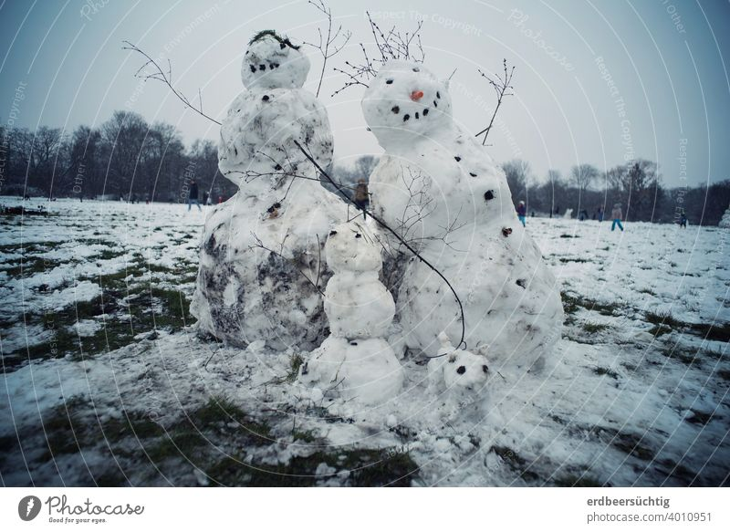 Happy snow family, built of snow and dirt on big meadow, leaning because it is already too warm Snow Ice Snowman snow woman Snow Child Family Snow Family