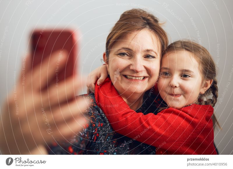Mother with her little daughter making video call using mobile phone. Woman and little girl talking with relatives. Cheerful family having fun taking selfie photo using smartphone