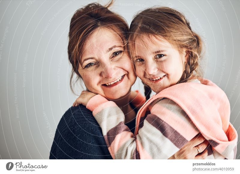 Happy mother and daughter embracing, hugging and smiling together. Family portrait. Happy moment. Woman and little girl posing to camera person child family