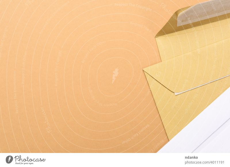 blank white paper brown and white envelopes on a brown background letter empty message office post card document mail postage stationery delivery communication