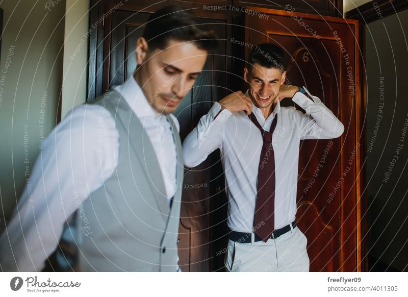 Groom and best man putting on the suit portrait groom wedding marriage engagement people young attractive copy space male 20s interior romance modern fashion
