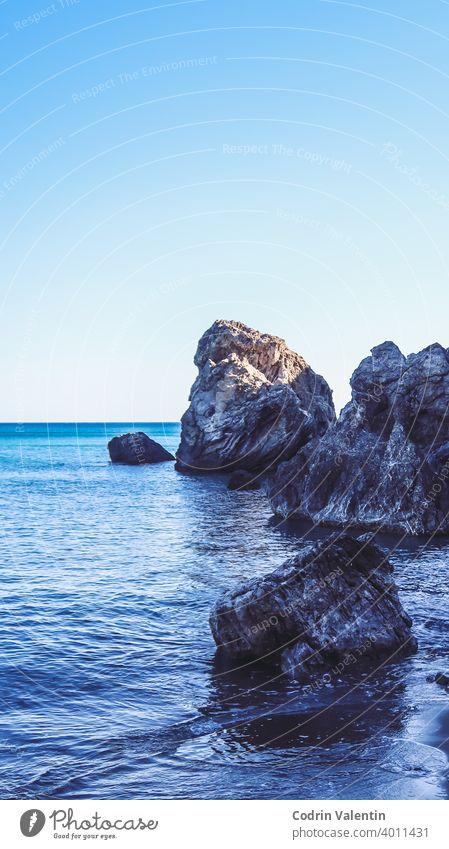 Seashore near a mountain with rocks and small waves bay beach bedrock blue body cliff coast coastal and oceanic landforms formation horizon island lake