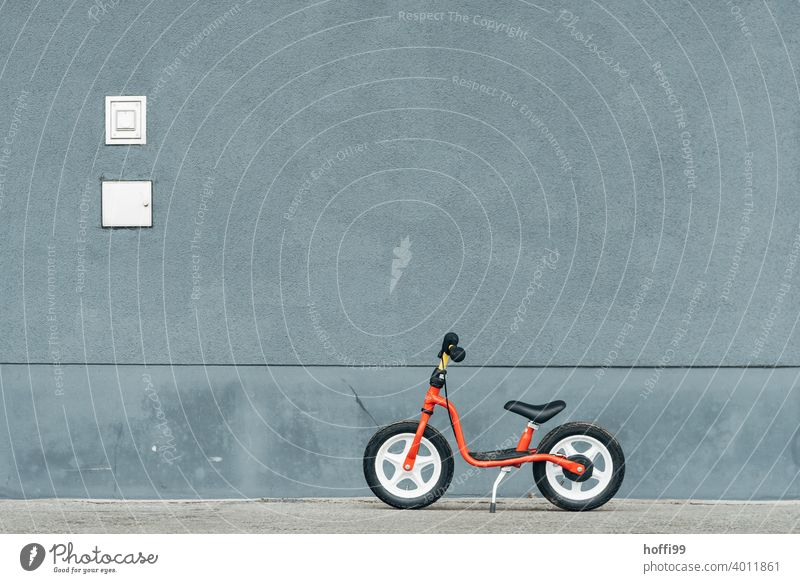 a red wheel, parked in front of a grey wall - pause impeller Children's bike child's playbike Red Minimalistic Bicycle Cycling Infancy Wheel Lifestyle Driving