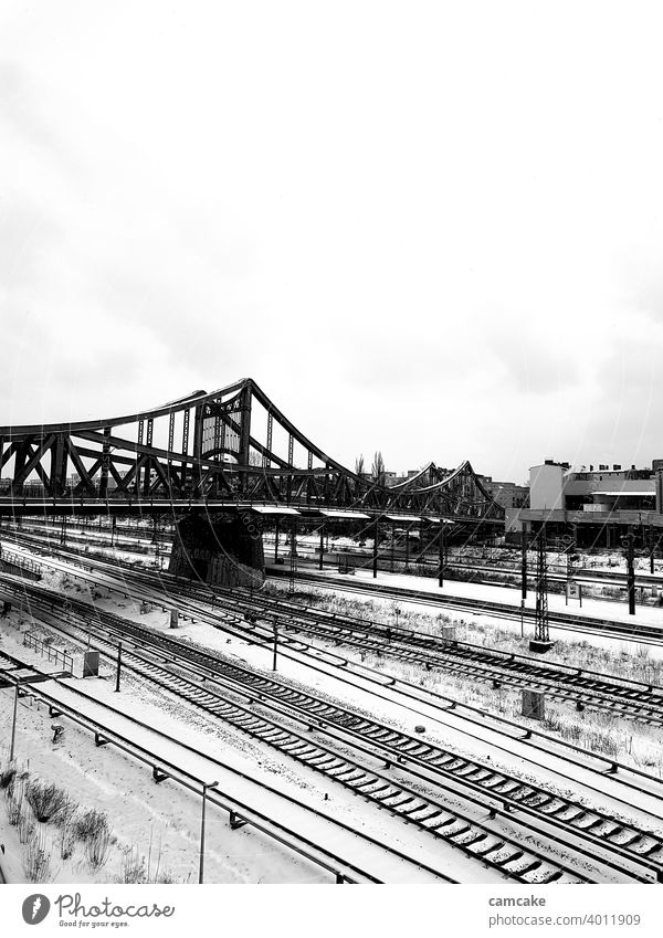 Bridge at the station with rail network in the snow Tracks Railroad system urban Town Winter Train Black & white photo Portrait format Gray scale value Light