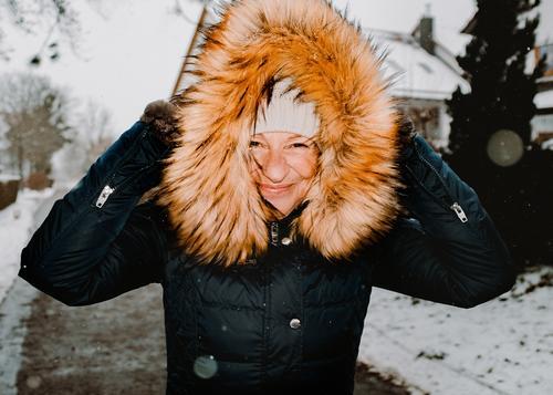 Frau spaziert bei Schneefall durch die Straßen spaziergehen walk winterwalk mantel kunstpelz lachen lächeln wärme schneefall kälte weiß jacke bäume dorf freude