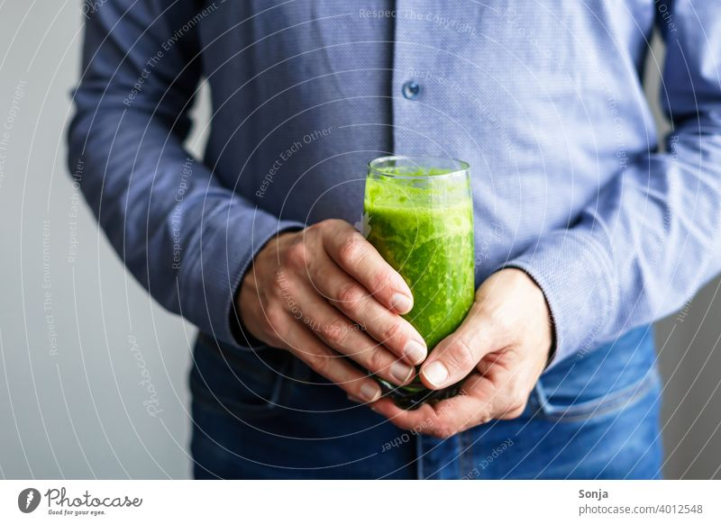 Man holding a glass of green smoothie in his hands Green Glass 50 plus Shirt Jeans partial view Hand stop Business Healthy Eating Vitamin Diet Vegetarian diet