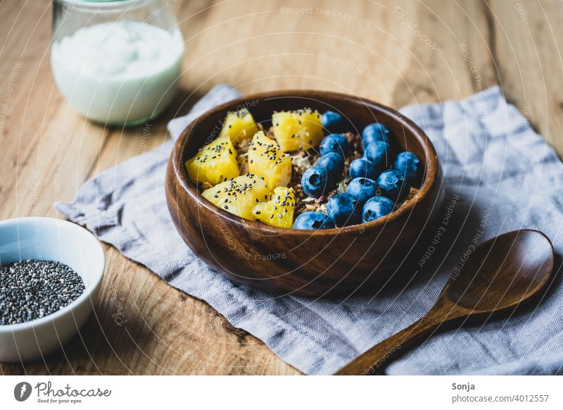 Muesli with blueberries and pineapple in a wooden bowl Cereal blueberry Pineapple Fresh Oat flakes Breakfast Healthy Eating Grain Organic produce Bowl Close-up