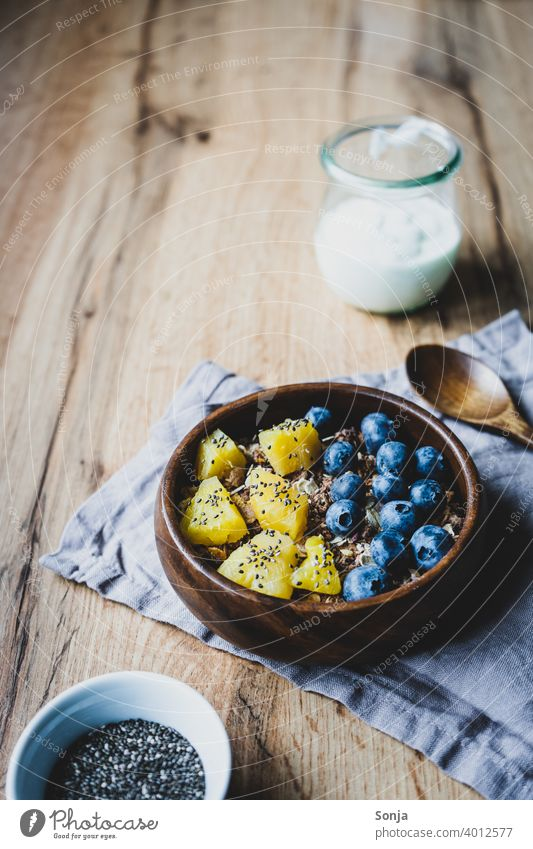 Healthy breakfast with muesli and fruit Cereal Oat flakes blueberry Pineapple breakfast table Breakfast Healthy Eating superfood Food photograph Table Wood