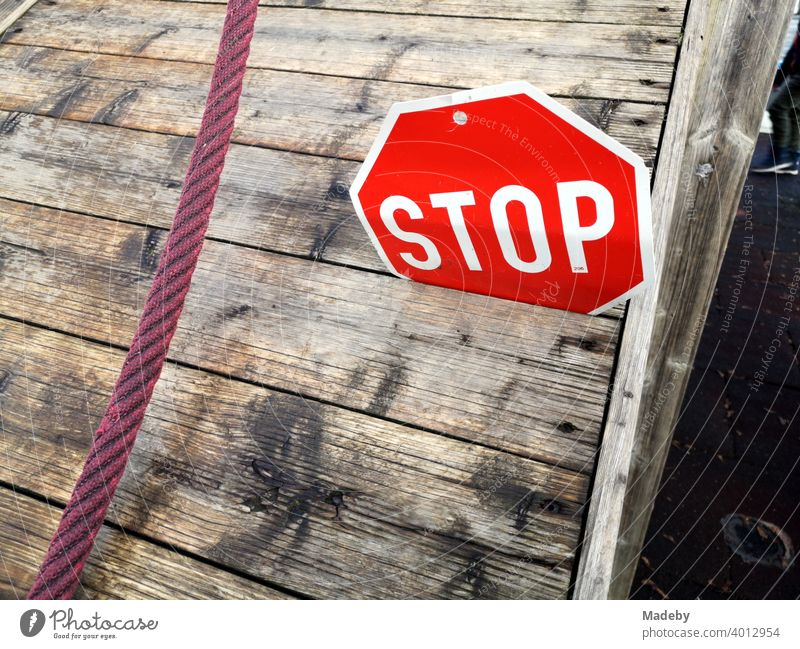 Stop sign made of sheet metal in the crack of a wooden platform with red rope on a children's playground at the elementary school in Wettenberg Krofdorf-Gleiberg near Giessen in Hesse, Germany