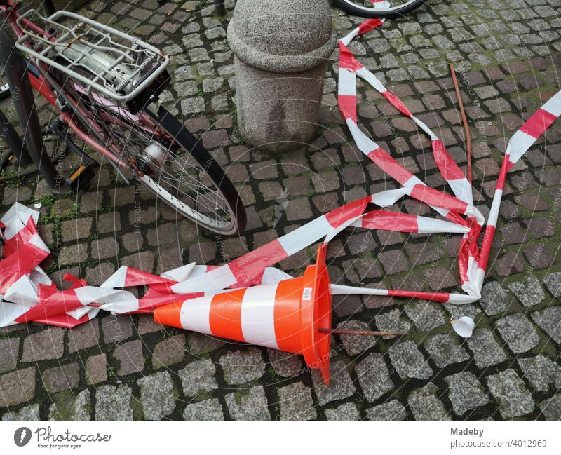Overturned Lübeck hat and torn red and white barrier tape on cobblestones in the city centre of Frankfurt am Main, Hesse Lübeck cone Skittle Traffic cone cordon