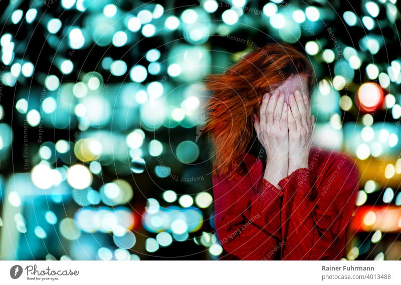 A red-haired woman holds her hands in front of her face. The bokeh of bright lights shines in the background. Woman problems clearer Headache Abstract