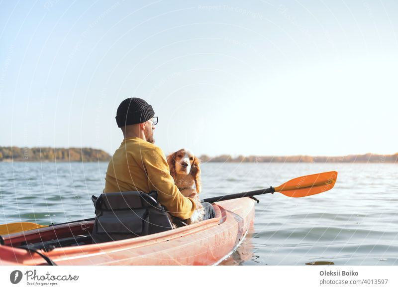 Man with a dog in a canoe on the lake. Young male person with spaniel in a kayak row boat, active free time with pets, companionship, adventure dogs 25-35 years