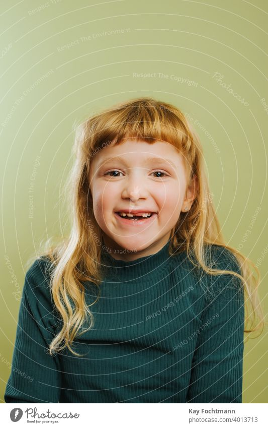 portrait of laughing blonde girl against green background bangs blond hair casual clothing child childhood colored background cute daughter emotion front view