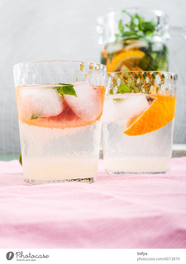 Fresh summer citrus drink in glasses with ice jar cocktail lemonade blood orange lime fruit background infused detox mocktail mint soda water sweet home made