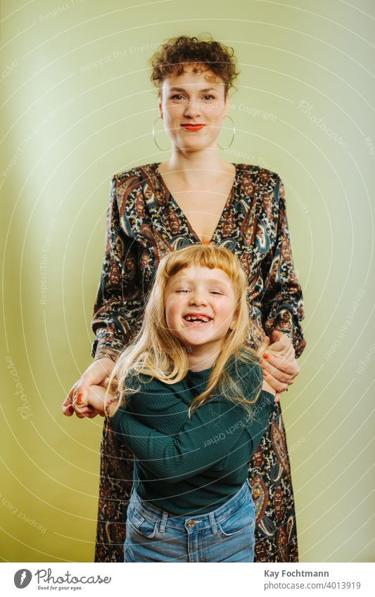 portrait of single mother and her pre-teen daughter against green background adult care caucasian cheerful child childhood cute emotion family female females