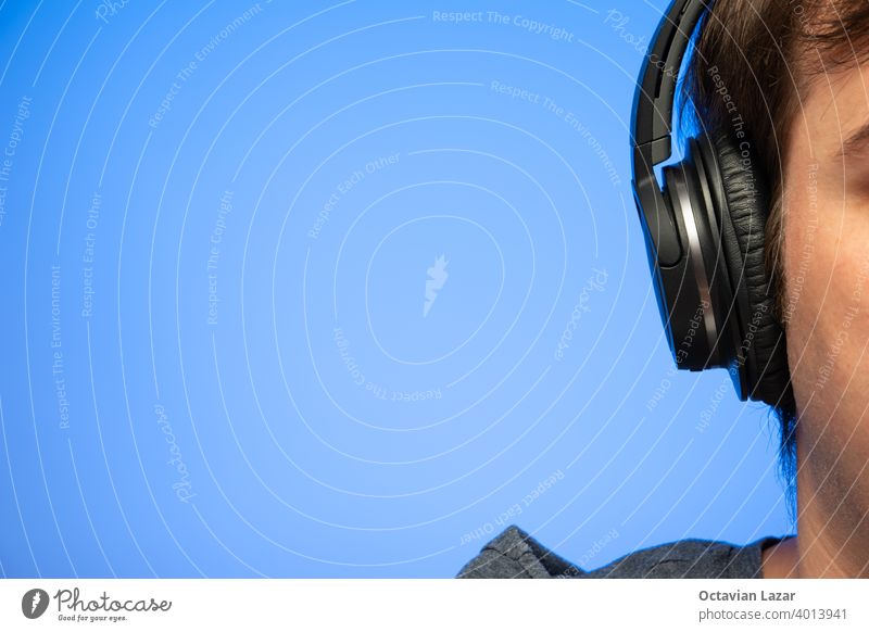 Unrecognizable cropped out Caucasian male head with black large headphones against blue background studio shot macro nobody man generic unrecognizable listening