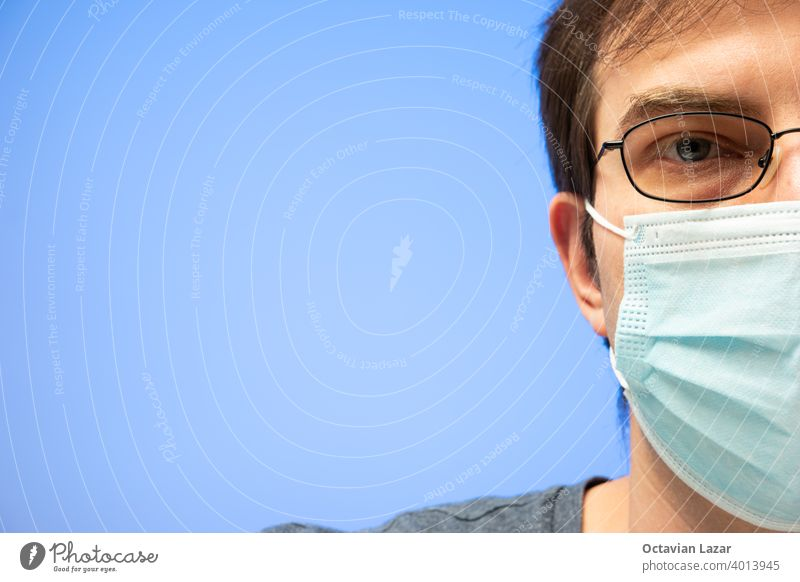 Caucasian male head with glasses and medical face mask studio portrait isolated on blue background health care looking mask sickness preventing respiratory