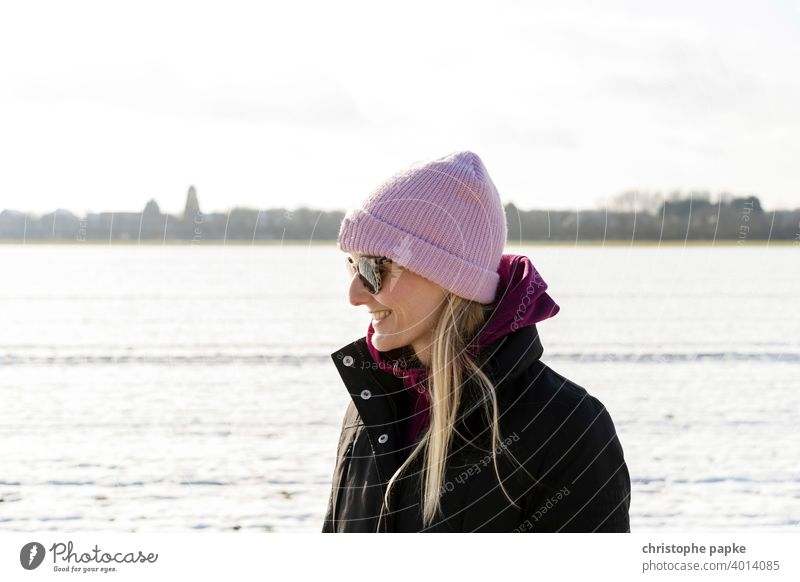 Woman with cap in snowy landscape Cap Cold Winter Smiling Blonde Sunglasses Bright portrait Young woman Exterior shot Snow Nature Colour photo Human being