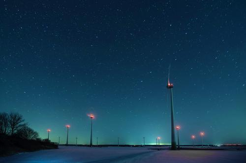 Winter night with starry sky above wind turbines on a snow-covered field Night Starry sky Big car windmills Snow Frost Long exposure Field Plain position lights