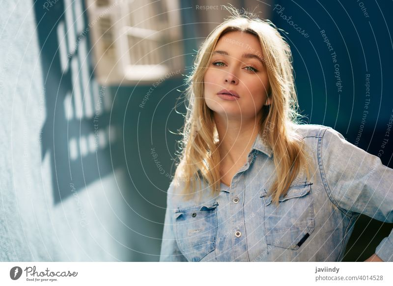 Portrait of blonde woman wearing denim shirt standing in the street. girl female russian blue eyes portrait fashion outdoors lady hairstyle person white pretty