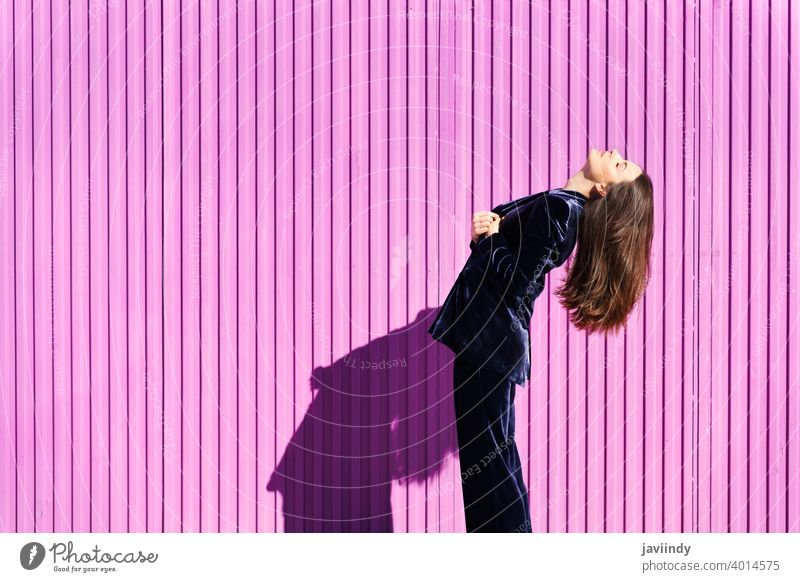 Woman wearing blue suit posing near pink shutter. woman hairstyle fashion model building blind fuchsia purple moving girl person lifestyle female urban