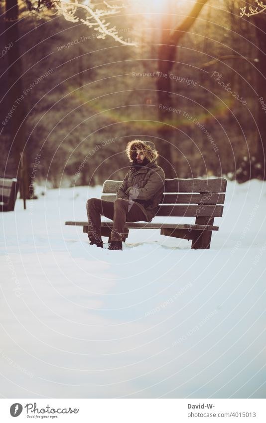 Man sitting freezing on bench in nature in freezing cold weather Freeze Winter Cold Snow White icily Winter's day Winter mood Bench Sit Nature onset of winter