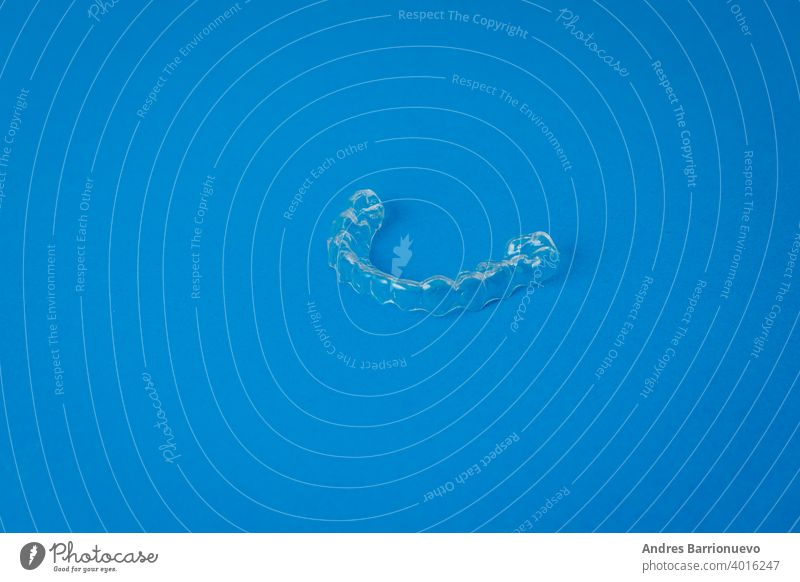 View of a transparent plastic dental appliance on a blue background technology dentistry prefabricated health denture treatment orthodontic oral trainer