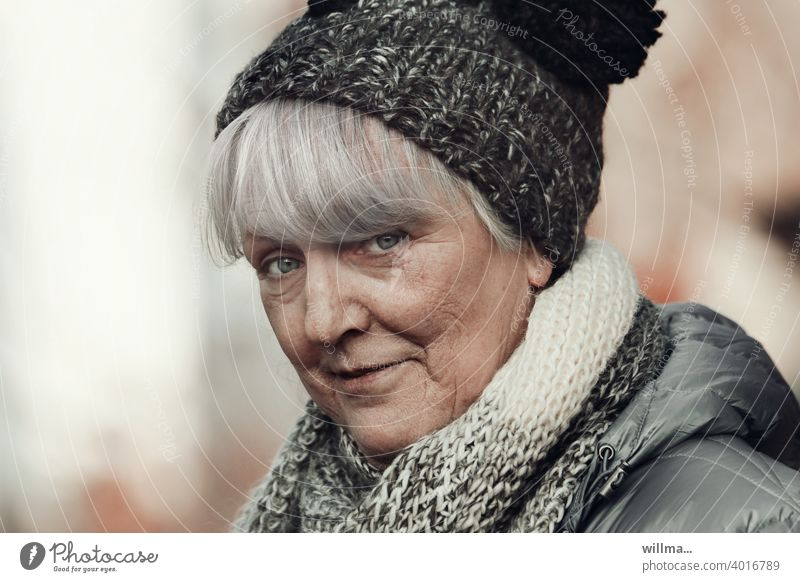 mischievous senior with bobble hat Senior citizen portrait White-haired Bobble hat Scarf Looking into the camera skeptical look skepticism Bangs asking