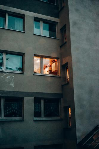 Facade of a residential building in the evening, light is burning in a window. Window Light Apartment Building Fassadr at home Evening Cozy dwell